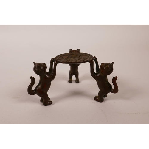 5 - A Chinese bronze of three cats holding a charger aloft, indistinct seal mark to base, 1½