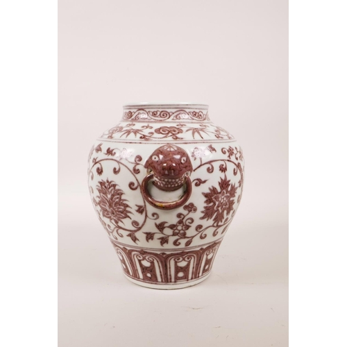 50 - A Chinese red and white porcelain vase with two mask handles and scrolling lotus flower decoration, ...