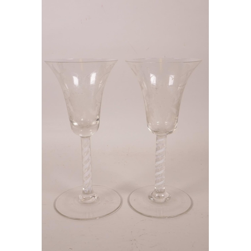 56 - A pair of Georgian style wine glasses with air twist stems and etched vine and bird decoration, 6½