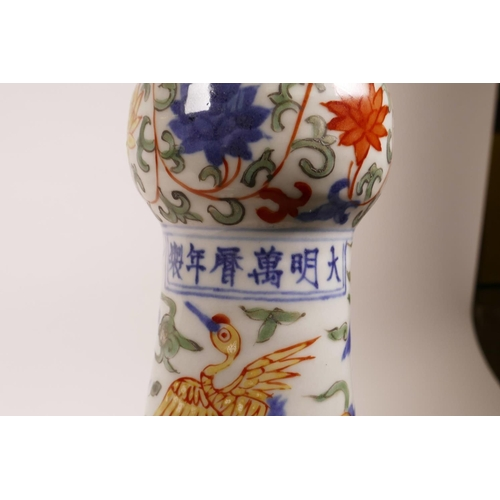 58 - A Chinese polychrome porcelain vase with a frilled rim, decorated with dragons and storks in flight,...