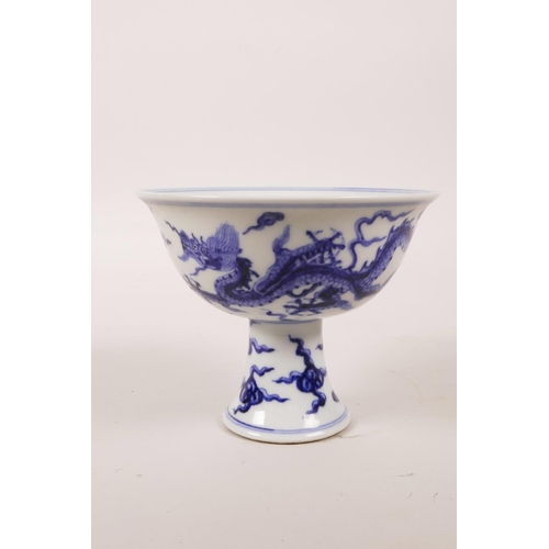 60 - A Chinese blue and white porcelain stem cup decorated with two dragons chasing the flaming pearl, 6 ...