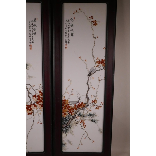 26 - A pair of Chinese porcelain panels decorated with insects on branches in bloom, mounted in painted h...