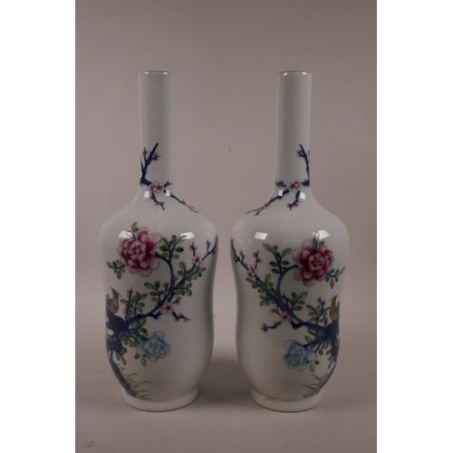 28 - A pair of Chinese polychrome porcelain vases with slender necks decorated with Asiatic birds amongst...