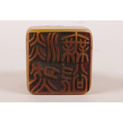 35 - A Chinese amber soapstone seal with a knop carved in the form of a horse, character inscription to s...