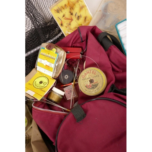 44 - A collection of fishing flies in three boxes and a tin, together with a landing net and a bog of mis...