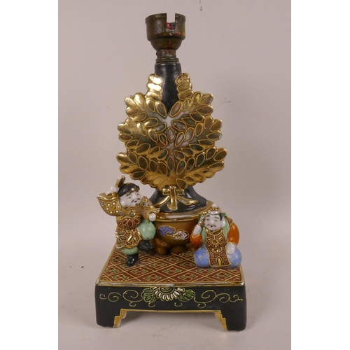 59 - A Japanese Meiji Satsuma lamp base moulded with two colourful figures before a large planter with gi...