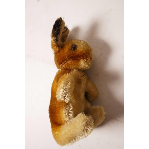 34 - A 1952/53 Steiff begging rabbit, golden mohair, fixed limbs, brown and black glass eyes, red stitchi...