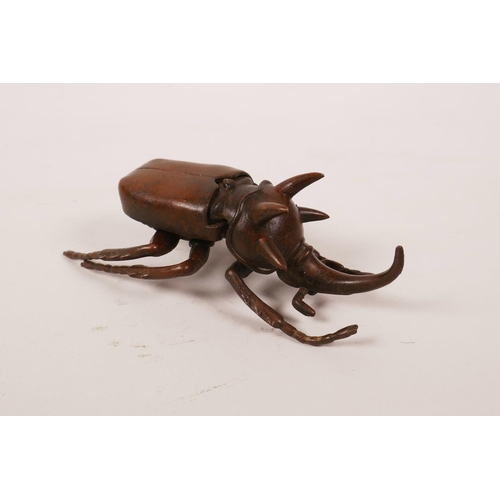 35 - A Japanese Jizai style bronze five horned rhinoceros beetle, the wings hinged to reveal a trinket bo...