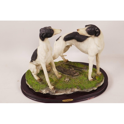 41 - A composition figure of two greyhounds on an oval wooden plinth, 8½