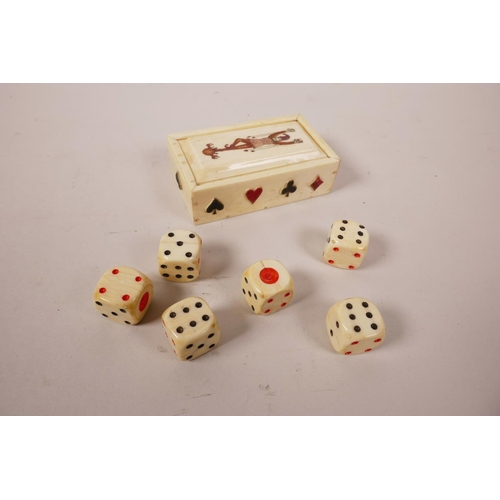 43 - A set of six faux bone dice in a bone case with playing card decoration, 3½