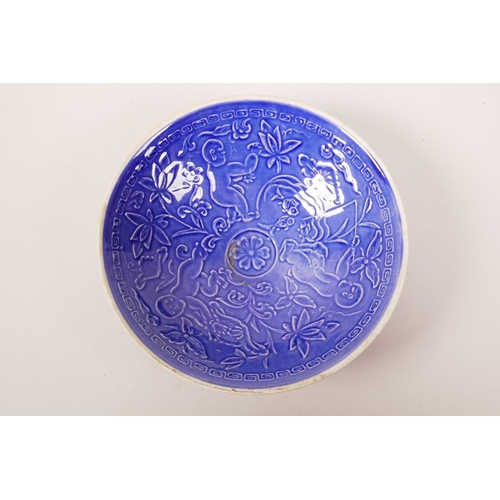 58 - A Chinese blue ground porcelain conical dish with underglaze decoration of a child at play, mark to ...