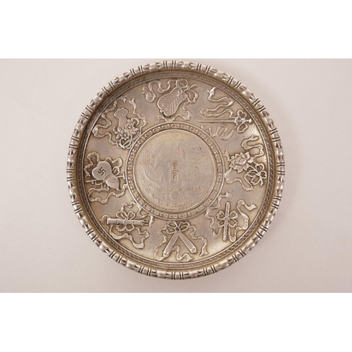 13 - A Chinese white metal coin dish with raised decoration of the emblems of the Eight Immortals, 3½