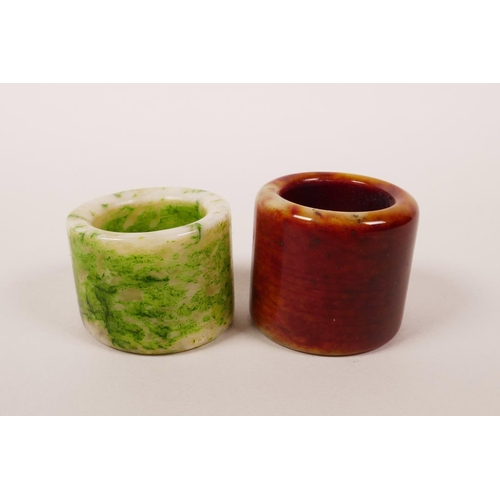 16 - A Chinese mottled green and white hardstone archer's thumb ring, and another similar...