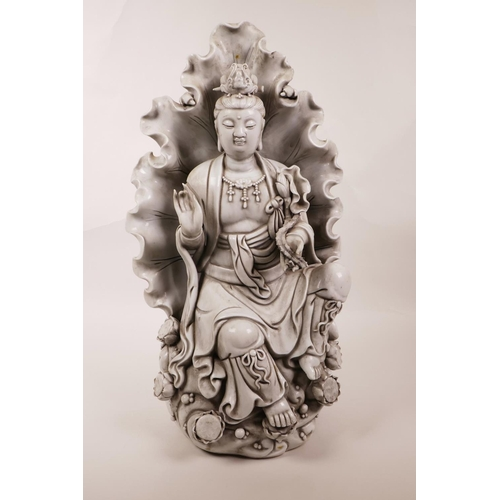 35 - A large Chinese blanc de chine figure of Quan Yin seated within a lotus leaf, impressed marks verso,...