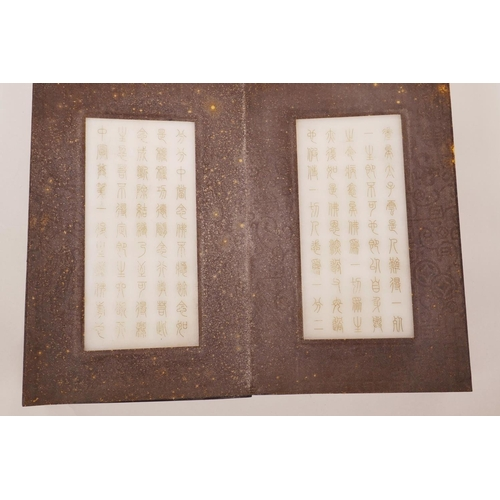 45 - A Chinese silk and hardwood bound book containing white jade tablets with engraved and gilt characte...