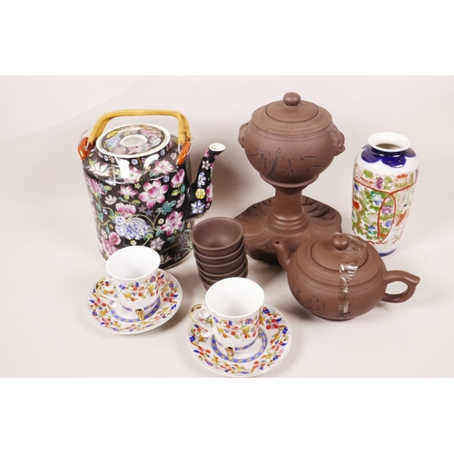 52 - A Chinese porcelain teapot painted with bright flowers on a black ground, 6½