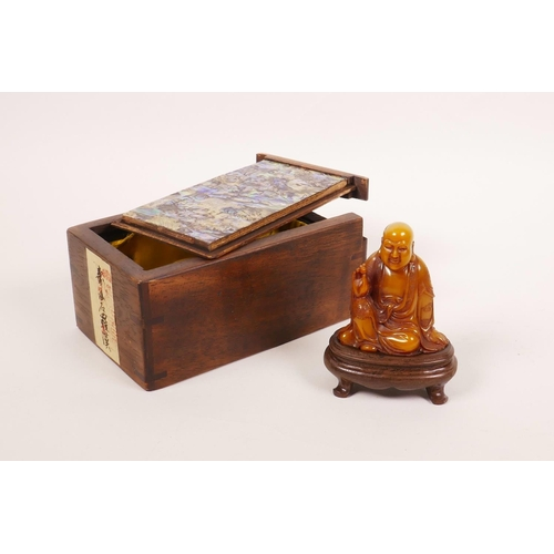 53 - A Chinese soapstone carving of Lohan, on a hardwood stand, with a fitted hardwood box decorated with...