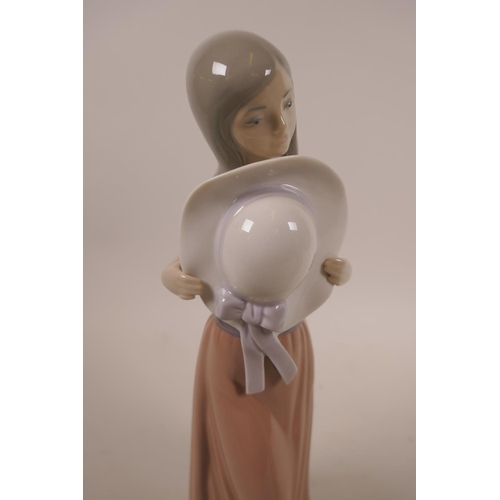 11 - Two Lladro figurines, 'Curious Girl with Straw Hat', #5009, and the other 'Bashful Girl with Straw H...