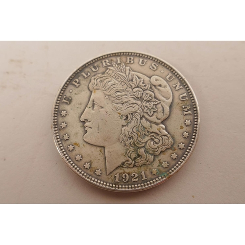 23 - A USA silver Morgan dollar coin minted in Philadelphia and dated 1921; a USA silver Kennedy 1964 hal...