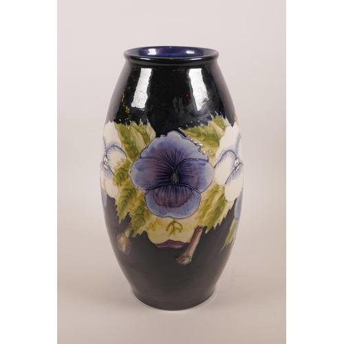 36 - A Moorcroft style blue glazed pottery vase with floral decoration, 12