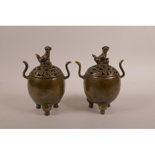 38 - A pair of Chinese bronze censers on tripod supports with two handles, pierced covers and a knop in t...