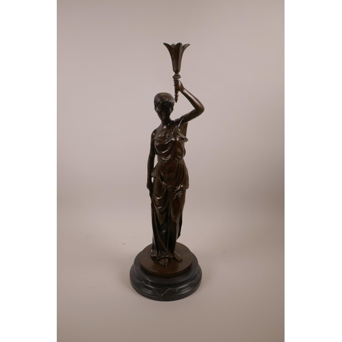 50 - A bronze figure of a classical lady holding a sceptre aloft, on a black marble base, 20