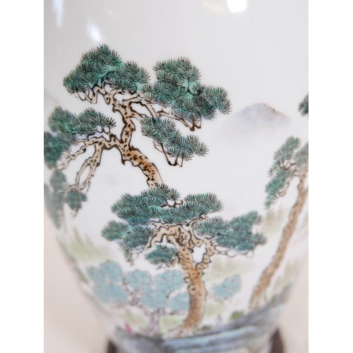 12 - A Chinese Republic porcelain vase decorated with figures in a forest and lake landscape, calligraphy...