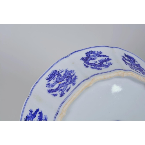 25 - A Chinese Ming style blue and white porcelain dish with lobed sides and dragon decoration, 6 charact...