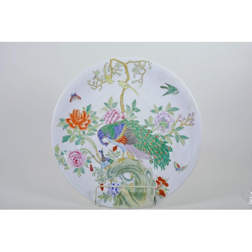 37 - A Chinese porcelain charger painted with peacocks in a flowering tree, seal mark to base, 14