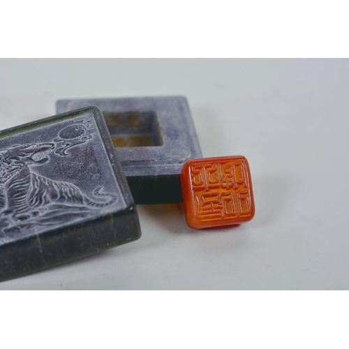 39 - A Chinese green soapstone box containing an amber stone seal, the cover carved with a tiger, 6 chara...