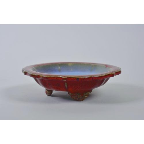 48 - A Chinese Jun ware dish on tripod feet with a lobed rim and flambé glaze, mark to base, 6½