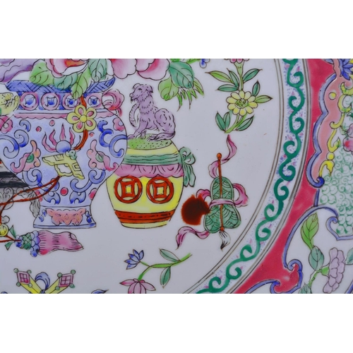 54 - A Chinese porcelain charger decorated with vases and flowers in the famille rose palette, red seal m...