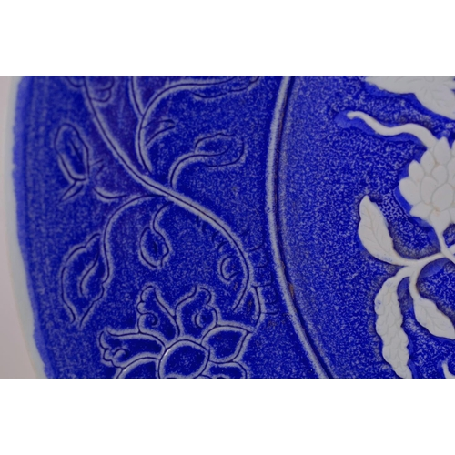 55 - A large Chinese blue and white pottery charger with raised and incised floral decoration, incised 4 ...
