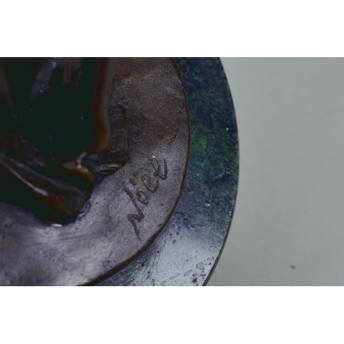 9 - A bronze figure of a girl standing in an artistic pose, marked Nöll, on a round marble stand, 12