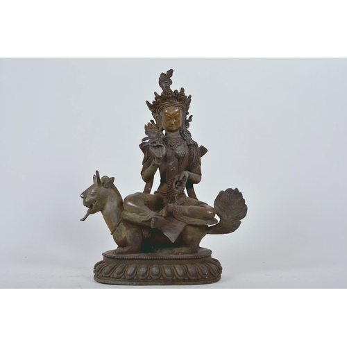 34 - A Chinese patinated bronze figure of Buddha seated on a mythical beast, 10
