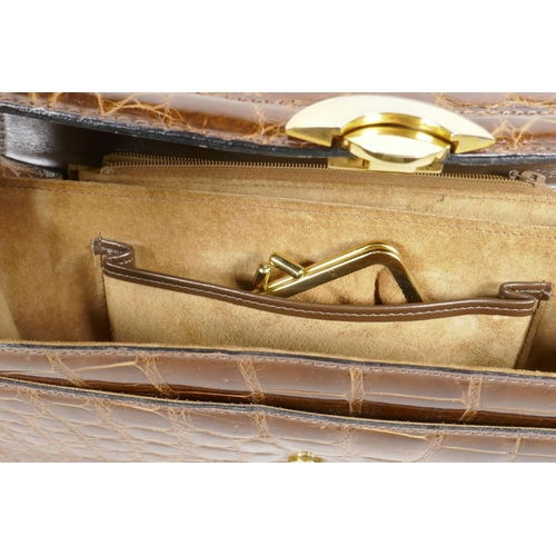 15 - A crocodile skin handbag with brass fittings and shoulder strap, 10