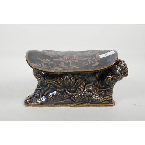 27 - A Chinese Cizhou kiln pottery head rest moulded in the form of a reclining figure, with blue black g...