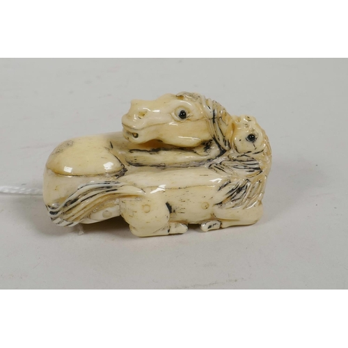 32 - A Japanese bone netsuke carved in the form  of a mare and foal, with glass eyes, signed, 2