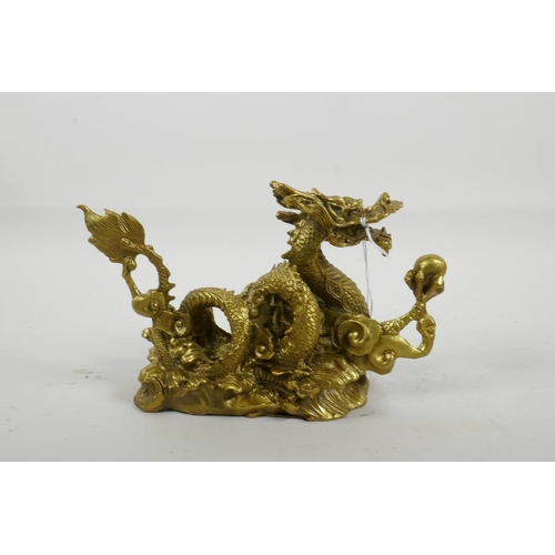 33 - A Chinese gilt metal figure of a dragon clutching the flaming pearl, 8