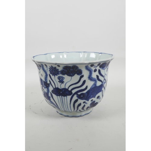 35 - A Chinese blue and white porcelain bowl with a lobed rim, decorated with carp in a lotus pond, six c...