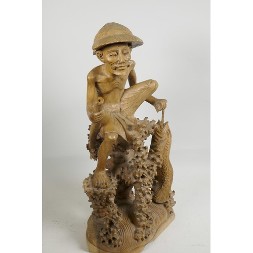 47 - An oriental carved wood figure of a fisherman with large fish, seated on a coral reef, 21