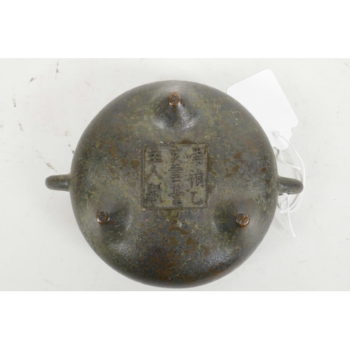 60 - A Chinese bronze two handled censer raised on three supports, with cast character mark to base, 4