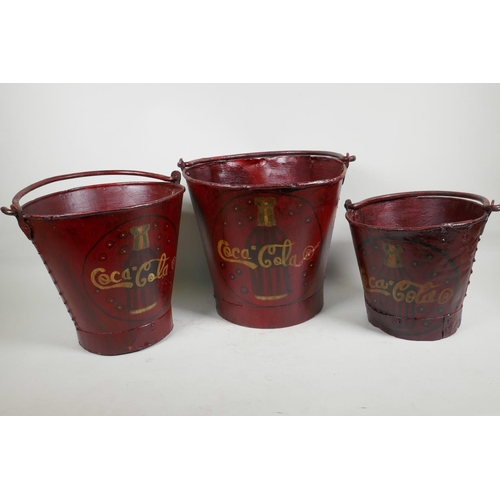 7 - Three graduated metal buckets painted with Coca Cola design, largest 10½