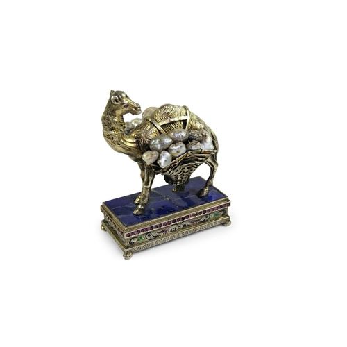 52 - Gem Set Camel  - A silver gilt figure of a camel. The camel carrying 2 baskets over his back, set wi...