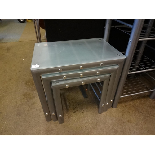 1 - Glass and stainless steel nest of three tables...