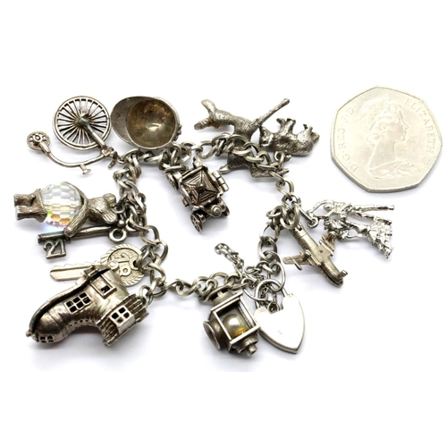 1006 - Sterling silver charm bracelet with 12 charms, 57g, padlock hallmarked silver. P&P Group 1 (£14+VAT ...