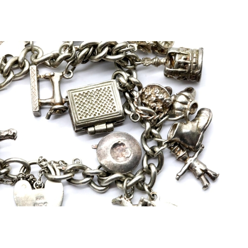 1011 - Sterling silver charm bracelet with 22 charms, approximately 84g total weight. Padlock hallmarked on...