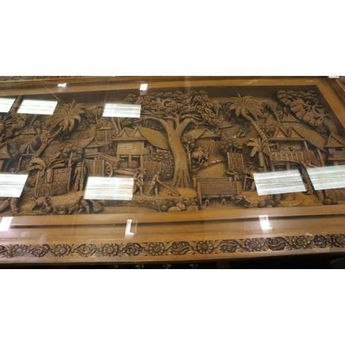 590 - A deeply carved substantial Oriental hardwood dining table with plate glass top displaying figures a...