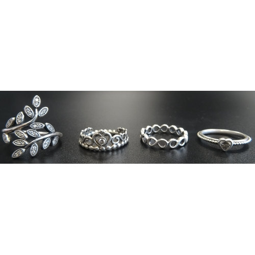 16 - FOUR PANDORA SILVER RINGS comprising Princess Tiara, Infinte, Delicate Heart and Shimmering Leaves (...
