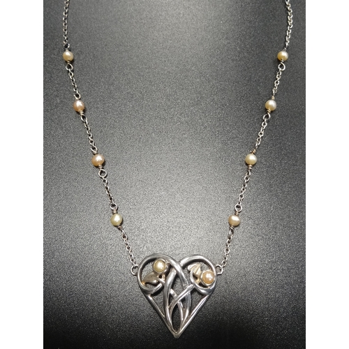 30 - SEED PEARL SET SILVER PENDANT the pierced heart pendant with entwined tendril decoration, on attache...